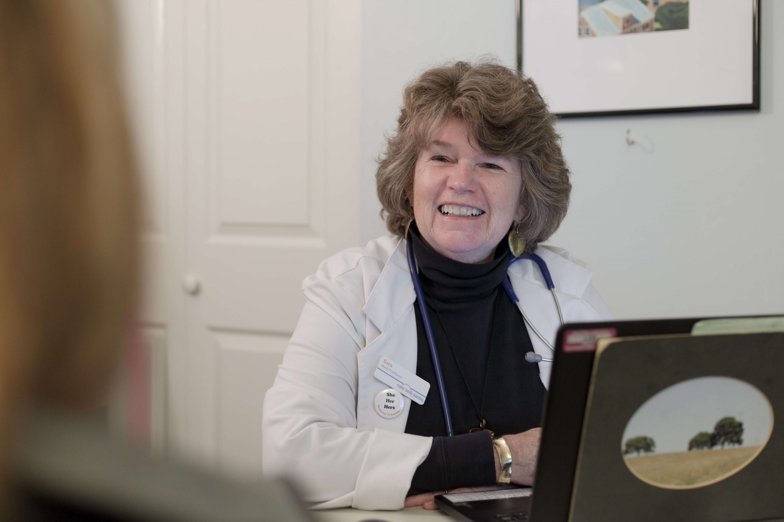 An MFP nurse practitioner sitting in front of an open laptop used for telehealth appointments.